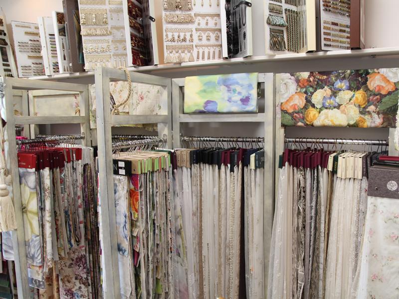 Образцы тканей на вешалках в салоне штор Прованс фото