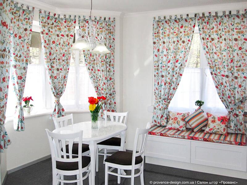 Светлые шторы с яркими цветами и подушками в полоску фото